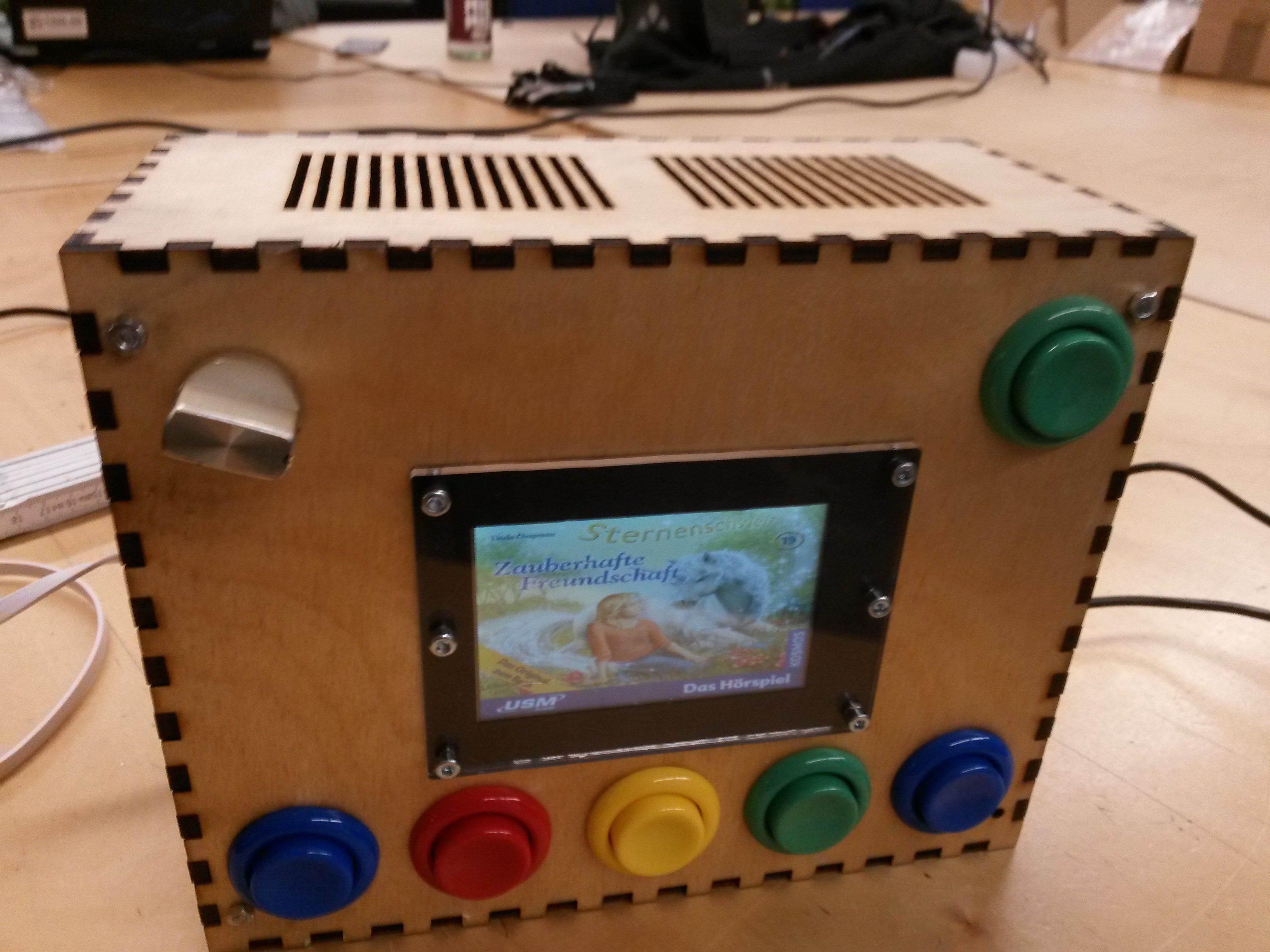 Picture of a lasercut wooden box with arcade buttons and a display. A media player for the little one